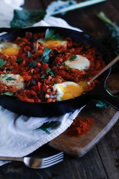 Shakshouka - a stewed tomato and vegetable sauce with poached eggs, #harissa, kale, and mushrooms!