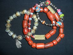 A necklace made custom featuring jasper beads and cast brass pieces. A Hamsa from Morocco with glass beads from Jersusalem in a bracelet. Femo beads of clay  in a bracelet mixed with cultured black pearls, also custom.