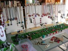 Clothespins holding necklaces and a strip of fake grass displaying bracelets and rings