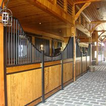 The dramatic swoop on these horse stalls gives the barn a beautiful aisleway. Lucas Equine horse stalls.
