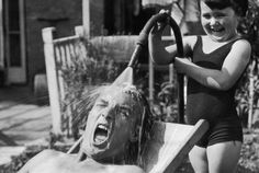 1936: A little girl takes great delight in drenching her dad with shockingly cold water from the garden hose as he sunbathes on a hot day.