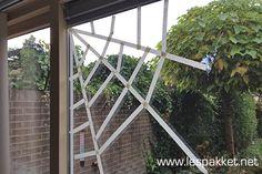 Neem een rol schilderstape en maak een spinnenweb op het raam. Maak vanuit de hoek eerst de 'spaken' van het spinnenweb, en plak vervolgens de korte stukken ertussen. Leuk voor het tentoonstellen van de geknutselde spinnen!