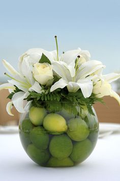 Cool way to incorporate uncut in season fruits in to a wedding centerpiece. Other fillers could include plums, small apples, lemons, nectarines whatever fruit or veggie is small enough and gives a nice compliment to the flowers