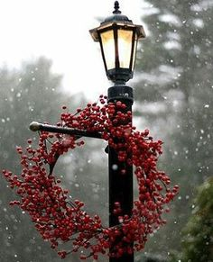 The start of snowflakes flutter around and silently fall on a red Berry Wreath.
