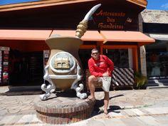 128 - Em Gramado, em frente a loja Artesanato das Bandeiras, que possui uma enorme cuia de chimarrão na sua entrada.