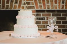 Pink and white wedding cake idea - wedding cake with swiss dot pattern and pastel pink rosettes {Priscilla Thomas Photography}