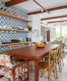 Cozinha tem parede revestida com ladrilho hidráulico geométrico e mesa de madeira.
