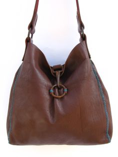 Soft supple brown leather bag with turquoise cross stitch gusset detail, old belting used for handles, and antique horse tack closure.