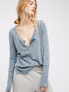 Gigi Henley | Super soft and comfy long sleeve henley tee featuring a cute rounded hem with subtle side vents for an effortless shape. Distressed edges create a perfectly lived-in look. Semi-sheer fabrication.