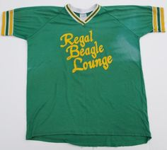 I want this!!!! Regal Beagle Lounge softball style Jersey shirt. Regal Beagle was the bar that Jack Tripper and the girls spent their nightlife in the television show Three's Company.  Shirt has some light staining across the front and a couple of small pin holes.  The waist hem has come undone in spots - see photos.