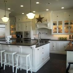 Floor to ceiling white shaker kitchen cabinets, white kitchen island with raised breakfast bar, honed black granite countertops, subway tiles backsplash, pot filler, white sawhorse stools, and schoolhouse pendants.