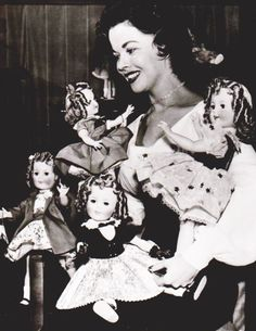 Shirley Temple and part of her collection of Shirley Temple dolls, 1957.