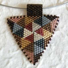 This TriangleScape Pendant design collection is called Quilts. There are 2 color palettes for this collection. Price is for purchase of ONLY ONE pendant. Please let me know in notes to seller which pendant you are buying.    These are beadwoven triangle pendants using japanese delica beads worked in peyote. Choose one of these color palettes:    Photo 1 & 2: Rainbow - silver, orange, pink, turquoise, mocha, burgundy, purple, moss green and cobalt blue. Photo 3: Rustic - chocolate brown, m...