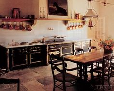 The kitchen of chefs Christine and Michel Guérard in Eugénie-les-Bains, France, was designed for both business and pleasure; the luxe range and cabinetry make a grand statement, while the country-style table and chairs complement the warmth and intimacy of meals truly savored.    Photographer: Gilles de Chabaneix  February 1991