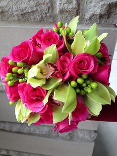 Orchids, roses and lime green hypericum berries for wedding bouquet