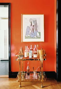 A brass bar cart sings against this tangerine wall.
