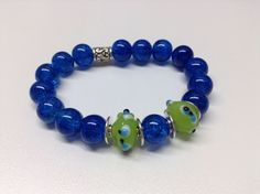 Bracelet #286 ($10)  Bracelet fait de verre bleu, vert et de billes de métal anti-ternissement monté sur un élastique.  Grandeur 7 pouces (18 cm):  -Bille de verre bleu de 10 mm  -Bille de verre vert de 14 mm -Bille de métal anti-ternissement. Fait main
