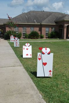 Instead of balloons, oversized playing cards lining driveway for Alice In Wonderland party! #aliceinwonderland