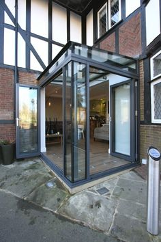 Maximising natural light within the riverside coffee shop with a small contemporary glass extension featuring aluminium bi fold doors and a structural glass roof.