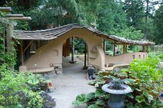 The cob arch in the middle of the garden is the entrance to a covered seating area and small cob guest house.