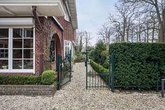Jaren30woningen.nl | Mooi voorbeeld van een typische jaren 30 tuin met grind, taxushagen, gemetselde muurtjes