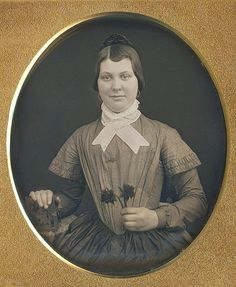 Very fine daguerreotype of a young lady, holding 2 flowers.