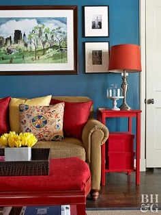 This living area plays to the three primary colors. A red ottoman, side table, and accent pillows ground the room, pulling the eye from one area to another. Blue walls offer a serene backdrop for the vibrant hue. A pop of yellow in a throw pillow and floral arrangement adds a ray of sunshine. All three colors are balanced and harmonize thanks to a shared jewel-tone value.