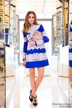 Olivia is wearing an Intarsia Stretch-Knit Dress and Rockstud Triple Clutch by Valentino