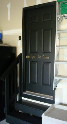 garage stairs and door black, with saying on door