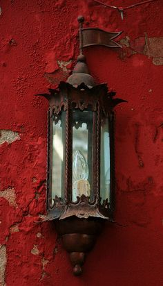 Beautiful rustic lamp on weathered red wall.