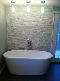 textured accent wall behind soaker tub