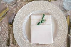 White Plateware with Sprig in Napkin    Photography: TimeFrozen Photography   Read More:  http://www.insideweddings.com/weddings/whimsical-shabby-chic-wedding-with-east-coast-charm-in-newport-ri/807/