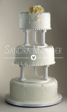 Classic pillared wedding cake with had piped swags and drops and beautiful handcrafted sugar roses