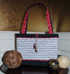 Crazy for Cadence is a custom order bag.  All cloth this cutie features black and white music score fabric with black and bright red polka dot accents.  A simple beaded tassel hangs on the front in coordinating colors.  Want to see the eye popping inside?  Head over to Facebook and find it at Bobbin My Thread!