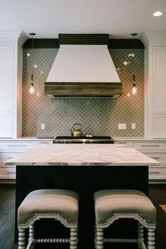 A white French kitchen hood accented with wood trim lines a gray herringbone tile backsplash illuminated by filament light pendants placed over a stainless steel stove.