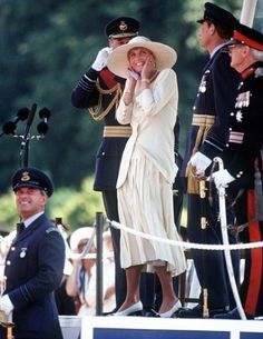 "Diana wearing a Catherine Walker designed ""colonial suit"" in cream Corisia washed silk with scooped neckline and pleated skirt at RAF Cranwell in July, 1991.  Diana covered her ears to protect herself from the noise of a Vulcan bomber during a fly-past at the end of a passing-out parade at the airbase."