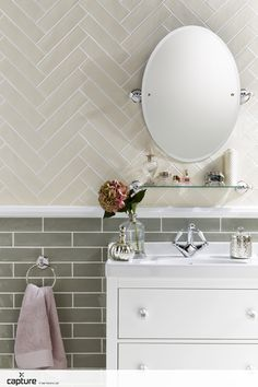 Tile inspiration for the bathroom. Soft cream tiles laid in a herringbone pattern with soft sage colour palette. White bathroom furniture, simple mirror and vintage style make the perfect bathroom photography. http://capture.setvisions.co.uk/Portfolio
