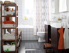 Baño con azulejos blancos en la pared y grises en el suelo, dos armarios para lavabo en negro-marrón, dos armarios de pared con puertas de espejo y unas estanterías en marrón oscuro.