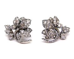 Pair of 19th century diamond flower cluster earrings, c.1860, set throughout with cushion cut stones, the stylised orchids upon a C scroll stem with leaf and bud to one side, mounted in silver and gold