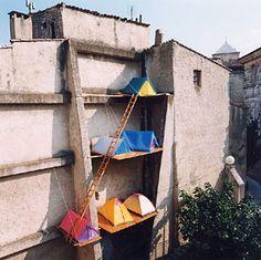 Samuel La Roze / Camping Urbain 1999 Six toiles de tente, plateaux de bois, échelle ; hauteur : 15 m Vue de l'installation Place de la Juiverie, Apt ( dans le cadre de l'exposition mise en place par l'association Plak'art : Lieux Communs ) Photographie Samuel La Roze