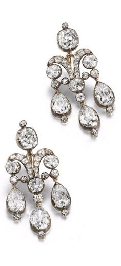 A pair of early 19th century girandole earrings. Each collet-set cushion-shaped diamond surmount suspending a scrolling old brilliant-cut diamond plaque, terminating in three pear-shaped diamond drops, mounted in silver and gold, diamonds approximately 11.70 carats total, later earring fittings, length 4.3cm, cased by Bulgari Roma