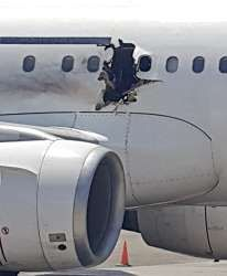 In this Tuesday, Feb. 2, 2016 photo, a hole is photographed in a plane operated ... - AP Photo