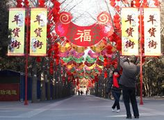 Chinese stroll under traditional Red Lanterns and Good Luck banners expressing good wishes for 2015.