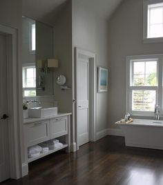 Master bathroom features a modern freestanding tub and modern floor mount tub filler placed under windows dressed in plantation shutters flanked by a water closet to the left.