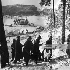 A French patrol with a Saint Bernard make their way through a beautiful snowy valley in France during World War II.