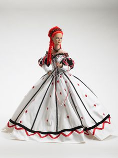 """Her majesty comes dressed in the finest court attire! The 16""""Queen of Diamonds features the Daphne Dimples® face sculpt and is crafted of high quality vinyl and hard plastic. She features hand painted face details, rooted red hair, white shantung, off the shoulder ball gown, with """"diamond"""" embroidery, red & black trims. A black headpiece with luminous red rhinestones adorns her head, along with matching black earrings and necklace. Black & red strappy pumps, red rhinestone encrusted scepter"""