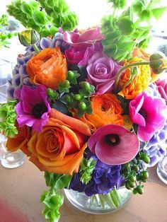 multi color floral bouquet - bells of ireland, orange roses, hydrangea, mauve calla lily, anemone, old fashioned roses, etc.