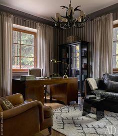 Кабинет, расположенный на первом этаже дома. Почти во всем доме стены покрашены краской — здесь же их решили оклеить обоями в полоску.