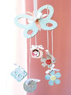 Baby Mobile  Covered chipboard shapes with pretty patterned paper create this baby mobile. Machine-stitching defines the outlines of the shapes, rickrack attaches the small shapes to the large butterfly, and bows add a bit of softness to the mobile.