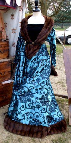 Abito in broccato azzurro perfilata di pelliccia di castoro. Il taglio è semplice ma la cura dei dettagli lo rende un abito prezioso. Costo £240